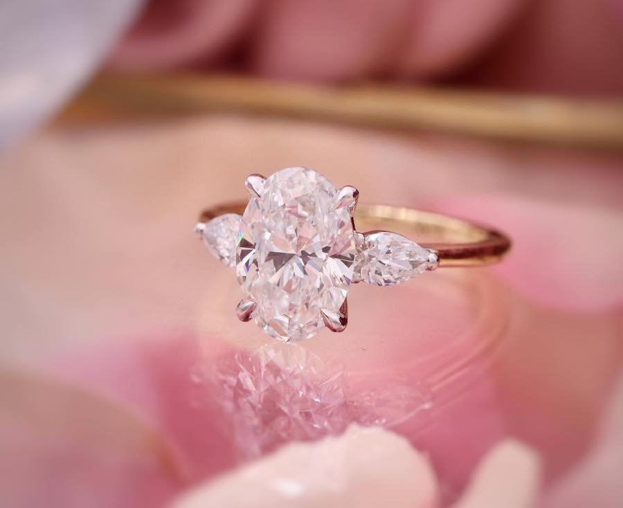 close up of an oval diamond engagement ring with pear shaped side stones