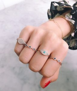 woman with evil eye symbol rings on each finger
