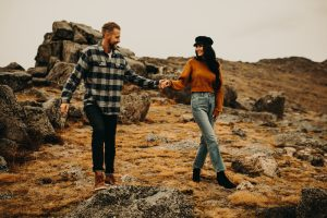 man and woman holding hands and looking at each other rocky landscape