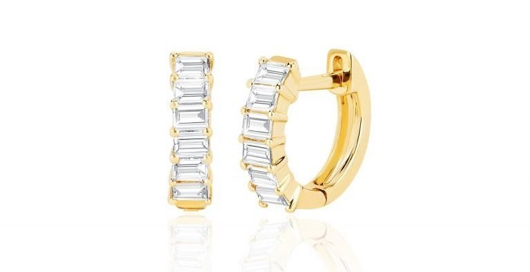 close up of gold and diamond baguette huggie earrings