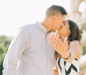 couple kissing as woman hold out her hand to show off her new engagement ring